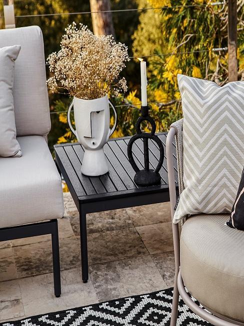 Kleiner schwarzer Gartentisch mit Dekovase und Kerzenständer