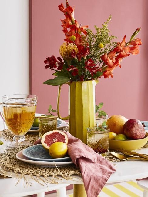 orange Blumen in gelbem Krug als Tischdeko für den Fruehstueckstisch