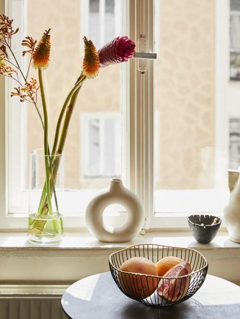 orange Schnittblumen in Glasvase auf dem Fensterbrett
