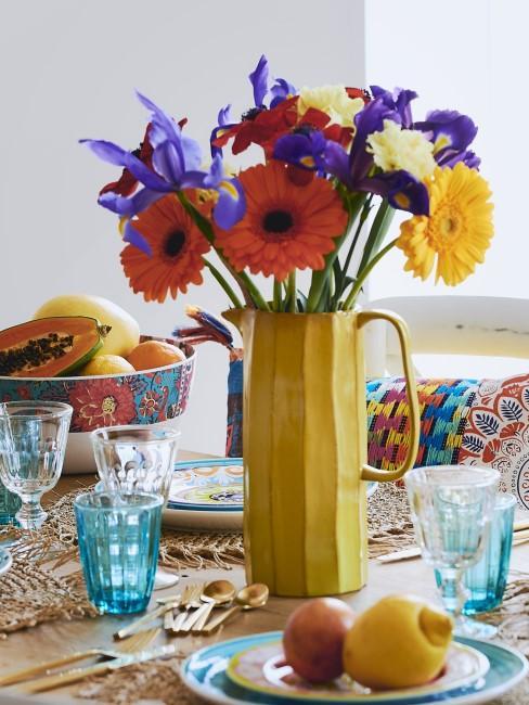 Sommerblumen in gelbem Krug auf dem Esstisch