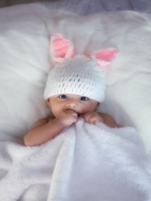 Baby schaut in Kamera mit Mütze mit Hasenohren
