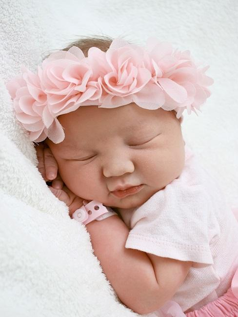 Kleines Baby schläft mit rosa Blumenkranz