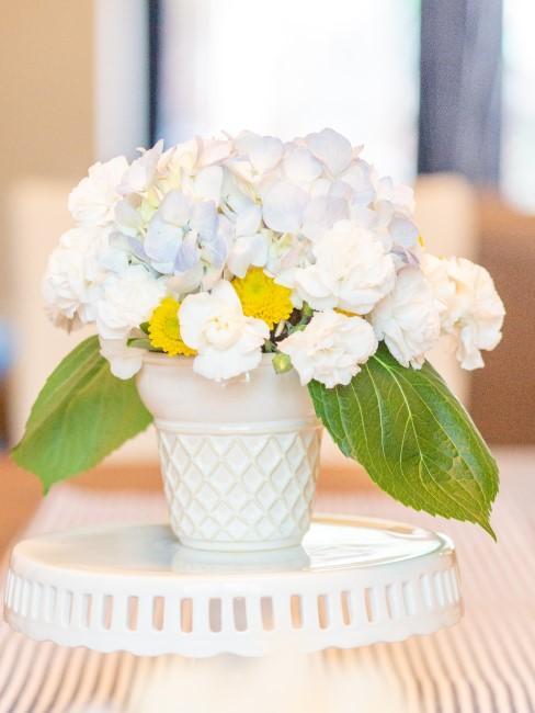 weiße Blumen in Becher auf Etagere als Tischdeko
