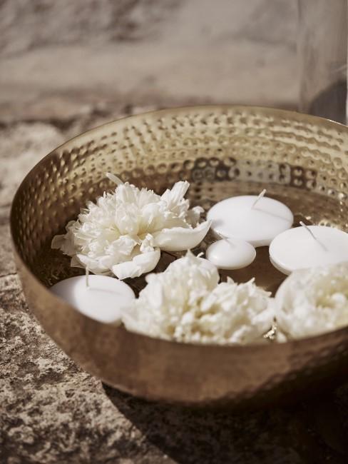 Weiße Blüten und Schwimmkerzen in Schale