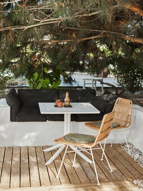 Kleiner weißer Gartentisch mit Deko und Sitzecke