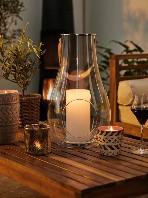 Gartentisch aus Holz mit Kerzen und gefülltem Weinglas
