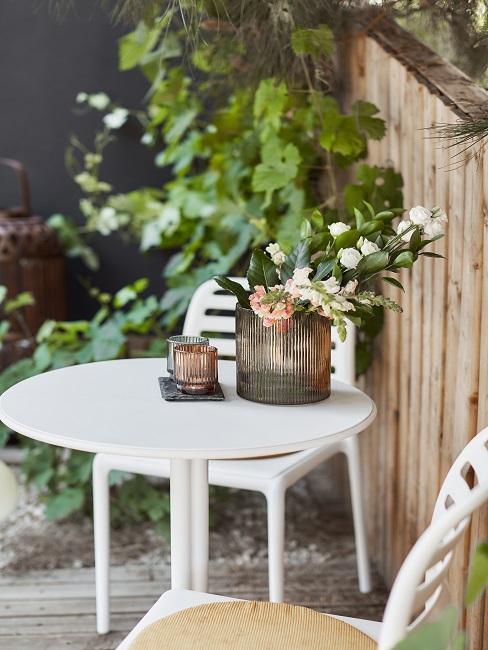 Kleiner weißer Gartentisch mit Blumen und Kerzenlichtern