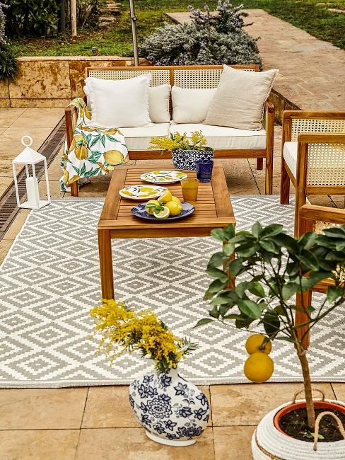 Gedeckter Gartentisch aus Holz mit Sitzecke