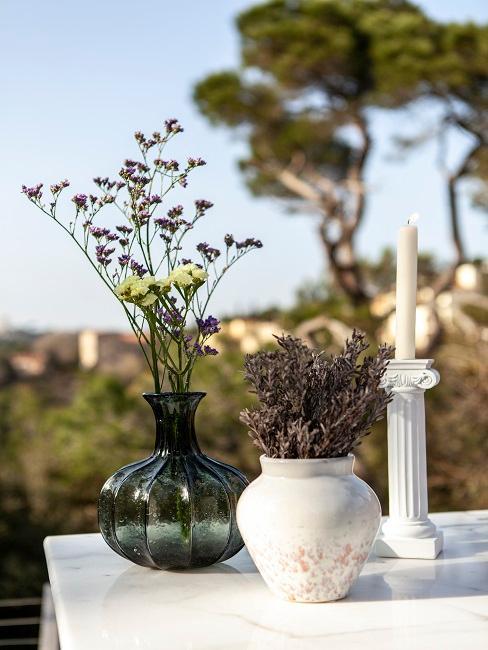Zwei kleine Vasen mit Blumenzweigen auf Gartentisch