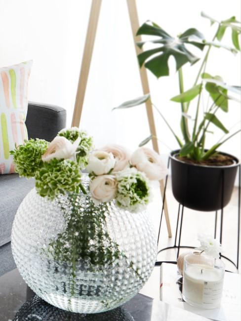 weiße und grüne Blumen in runder Glasvase