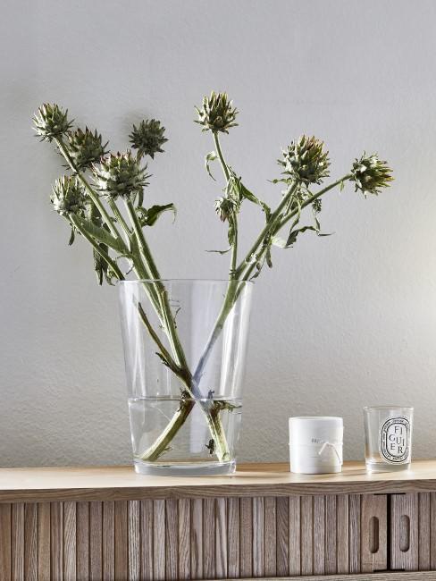 grüne Blumen in einer Glasvase auf einer Konsole