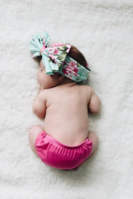 Baby liegt auf dem Bauch auf weißem Teppich
