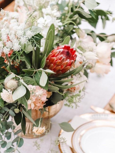 Blumengesteck mit weißen Blumen und roter Protea als Tischdeko