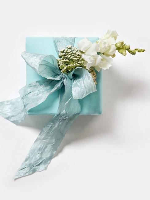 weiße Blume als Deko-Element auf einem Geschenk