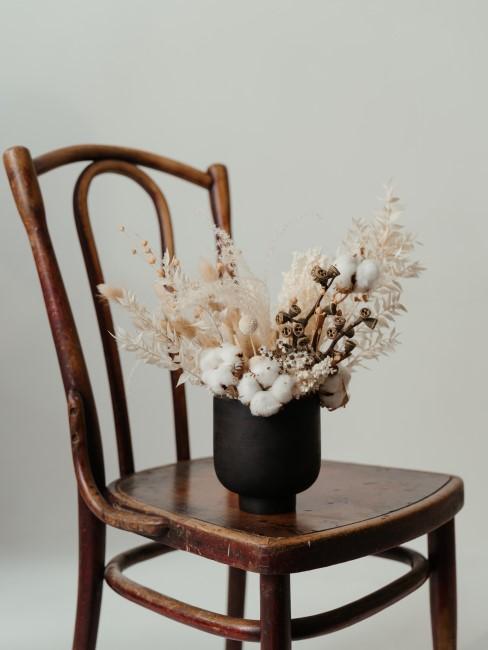 weißer Trockenblumenstrauß mit Baumwolle in Vase auf Holzstuhl