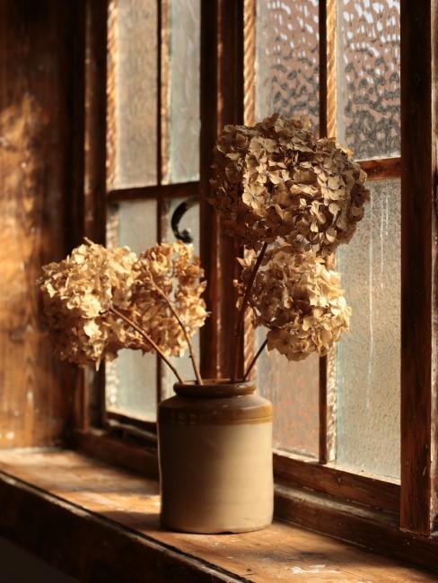 getrocknete weiße Hortensien in Vase auf dem Fensterbrett