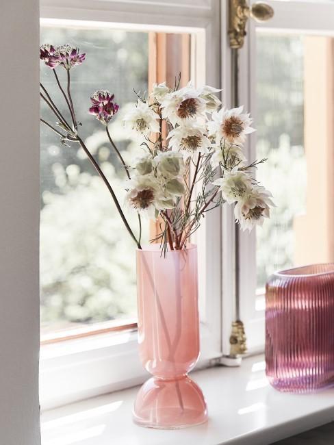 weiße Trockenblumen in Glasvase auf dem Fensterbrett