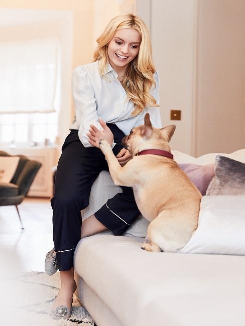 Blonde Frau und Hund berühren sich mit Hand und Pfote