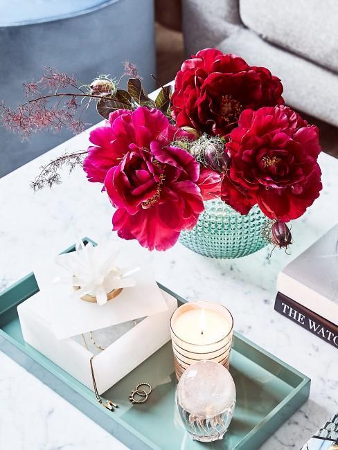 rote Blumen in Vase auf Couchtisch
