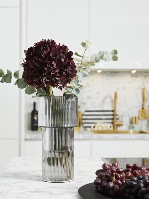 dunkelrote Hortensie in Glasvase neben Teller mit Trauben