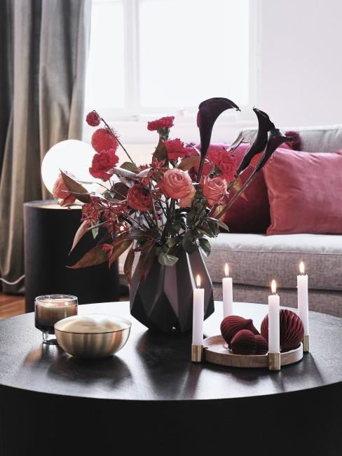 rote Blumen in Vase auf dem Couchtisch mit Kerzen