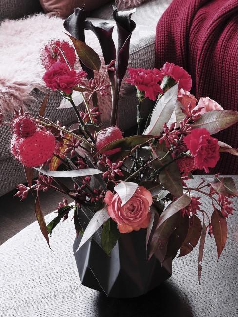 rote Blumen in Vase auf dem Couchtisch