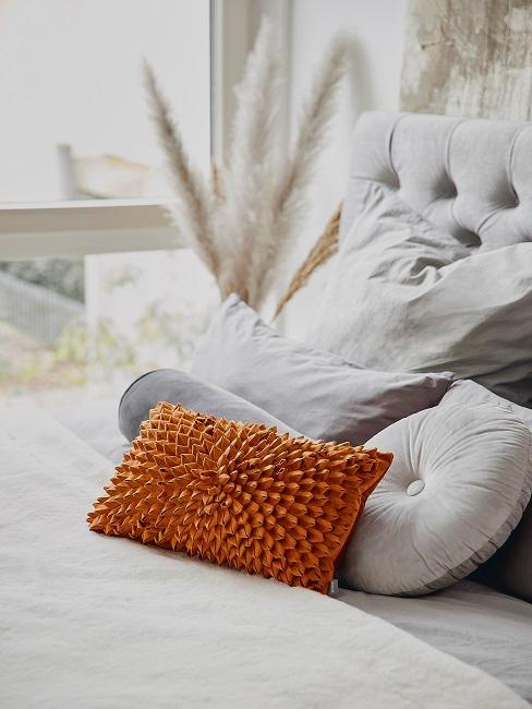 Hellgraues Bett mit grauen und orangenen Kissen