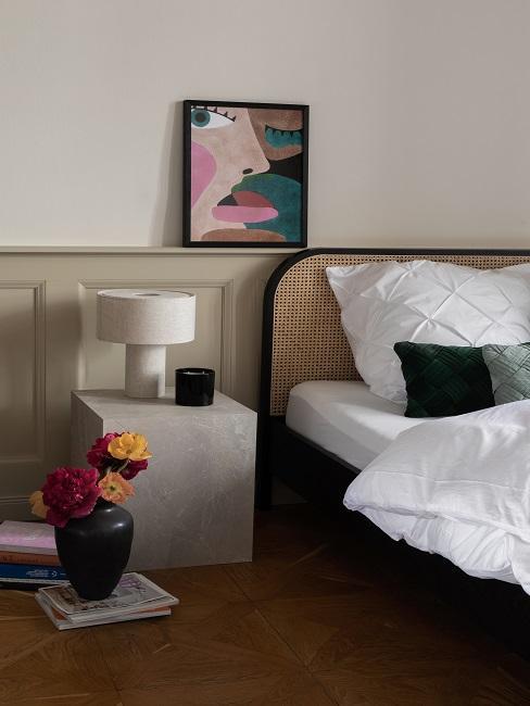 Schlafzimmer mit Bett grauem Beistelltisch und abstraktem Bild
