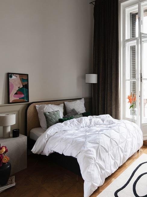 Kleines Bett mit weißer Bettwäsche und Kissen in Petrol