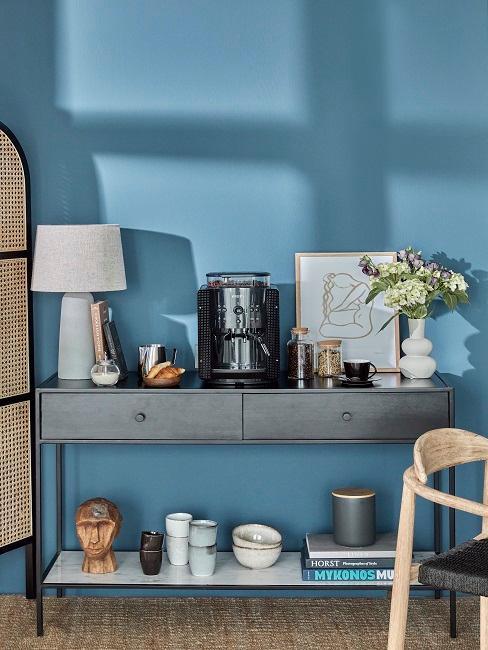 Kleines Sideboard mit Deko vor blauer Wand