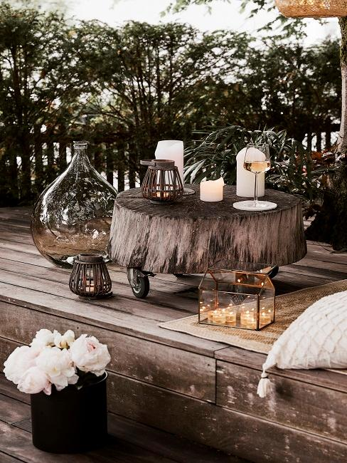 Kleiner runder Tisch auf Holzterrasse mit Deko