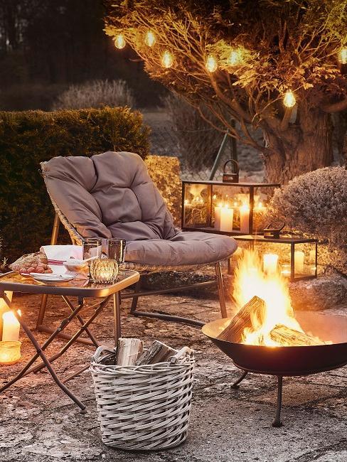 Brennende Feuerstelle im Garten mit Kerzen und Gartenstuhl