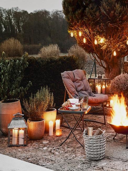 Feuerstelle im Garten mit Kerzen und Gartenstuhl