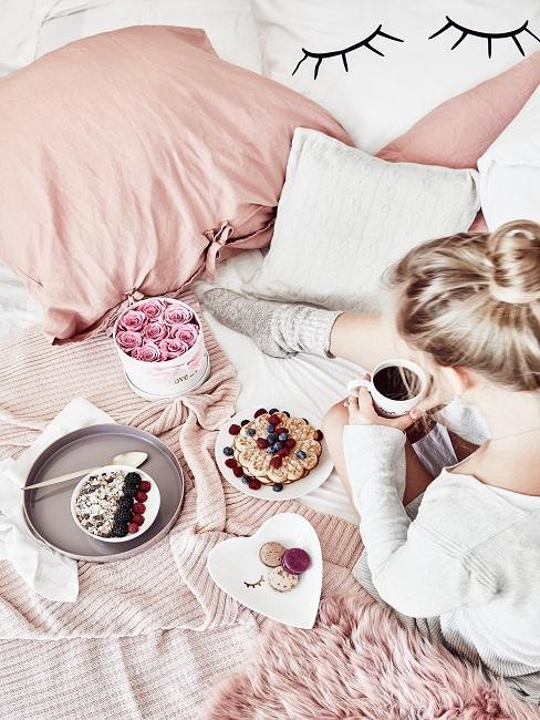 Frau sitzt mit Kaffee und Frühstück am Morgen im Bett
