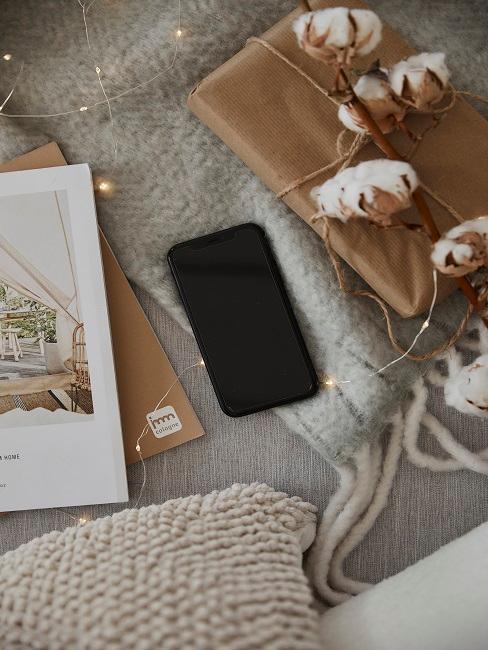 Iphone auf dem Bett mit Geschenk und Zeitschrift
