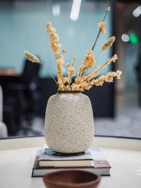 Vase und Trockenblumen auf einem Tisch