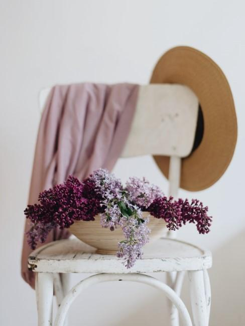 Lila Blumen auf weißem Shabby Chic Stuhl