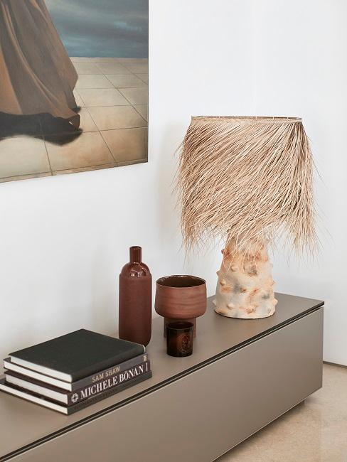 Sideboard mit einer Palmenlampe und verschiedenen Vasen