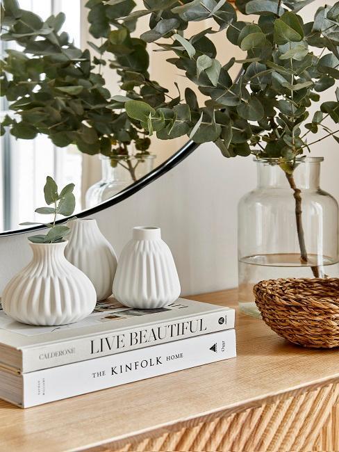 Kleine weiße Vasen auf einigen Coffee Table Books