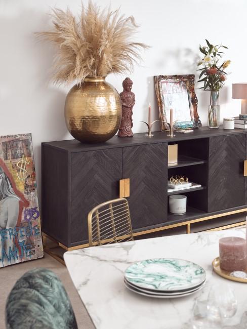Kommode aus dunklem Holz und goldene Deko