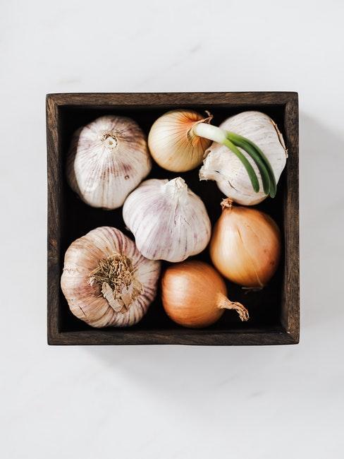 Knoblauch und Zwiebeln in einer Holzschale vor weißem Hintergrund