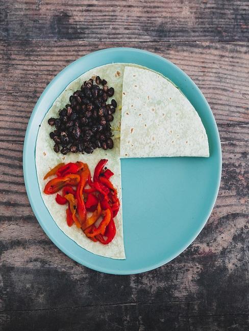 Tortilla auf einem blauen Teller mit Paprika und Bohnen