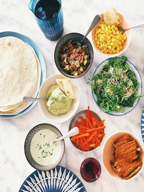 Tortilla mit verschiedenem Gemüsen und einem Dip auf dem Tisch