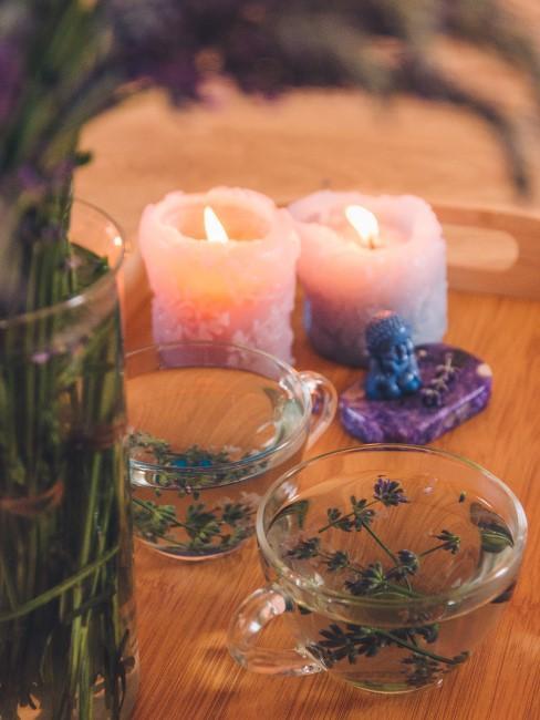 Lavendel in Teetassen und Vase mit Kerzen
