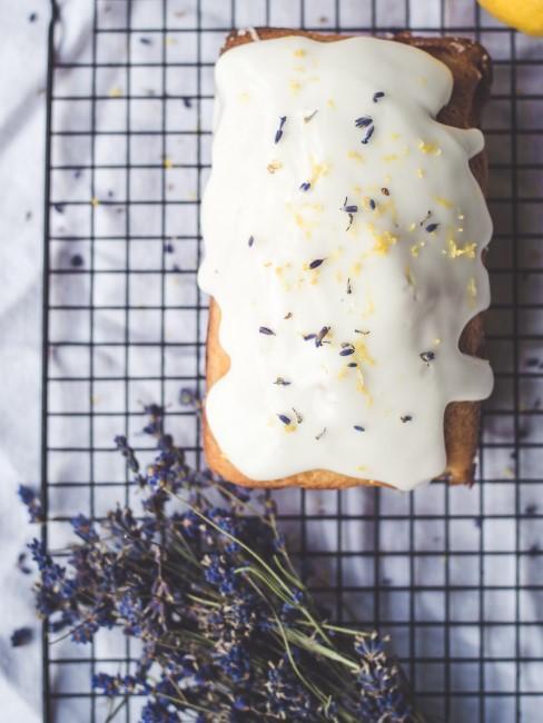 Lavendel neben Zitronenkuchen mit Glasur