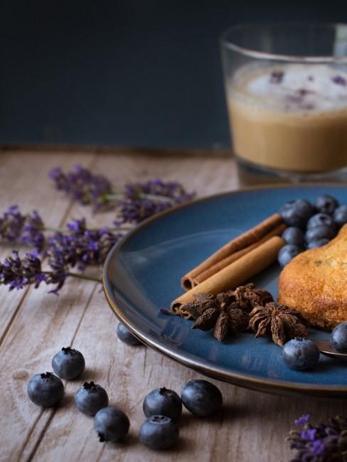 Lavendel neben Teller mit Heidelbeeren und Kaffee