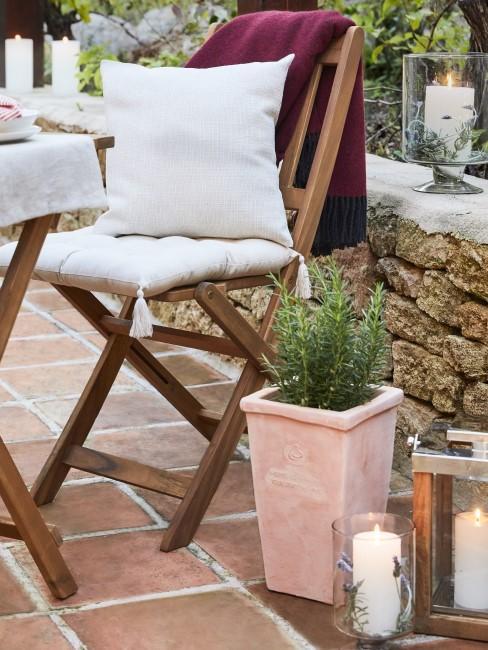 Lavendel und Kerze im Glas neben Stuhl und Blumentopf