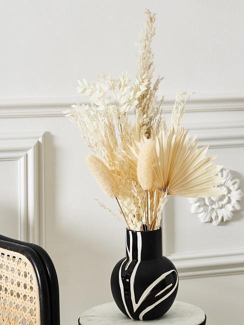 Weiße Trockenblumen in einer schwarzen Vase