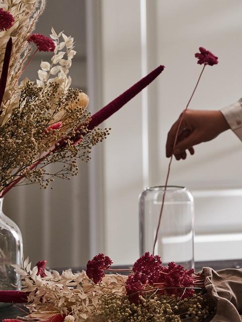 Frau steckt einzelne Trockenblumen in eine Vase