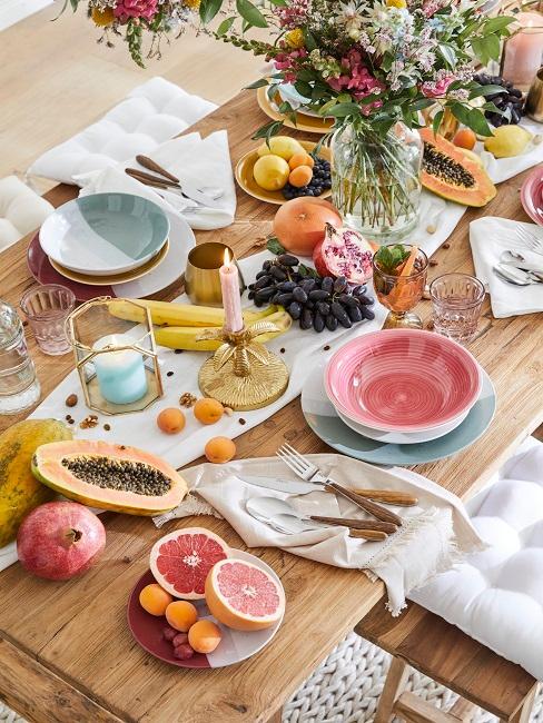 Bunt gedeckter Tisch mit Früchten und Blumen